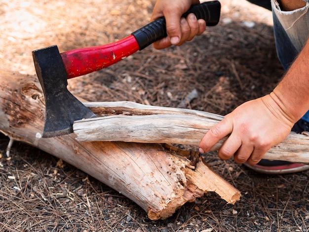 Hombre de cosecha cortando enganches en el bosque