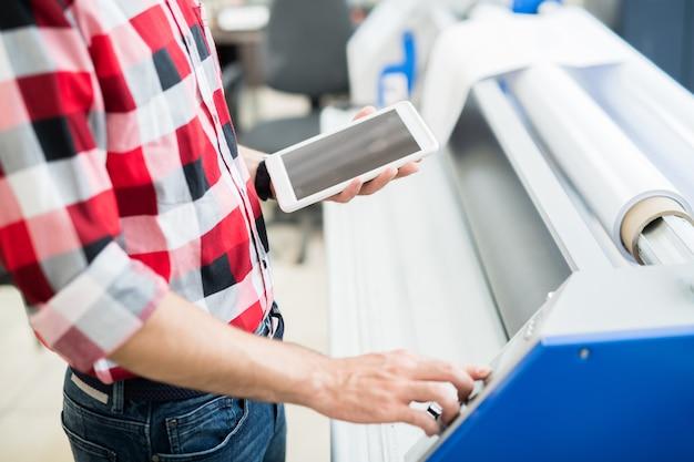 Hombre de cosecha con tableta con equipo de impresión