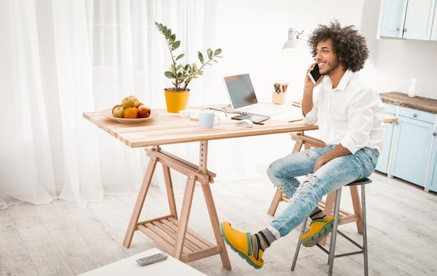 Hombre creativo habla por teléfono móvil trabajando desde casa.