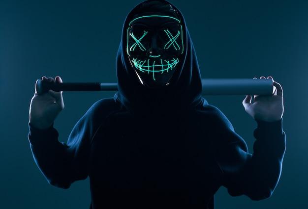 Hombre criminal anónimo con bate de béisbol en una sudadera con capucha negra y máscara de neón