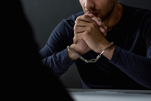 Hombre criminal con esposas en sala de interrogatorios.