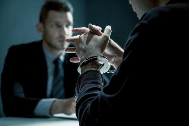 Hombre criminal con esposas siendo entrevistado en la sala de interrogatorios