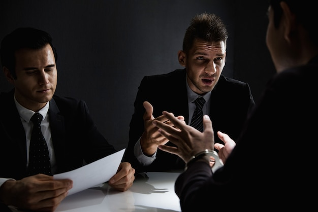 Hombre criminal siendo entrevistado en la sala de interrogatorios después de cometido un crimen