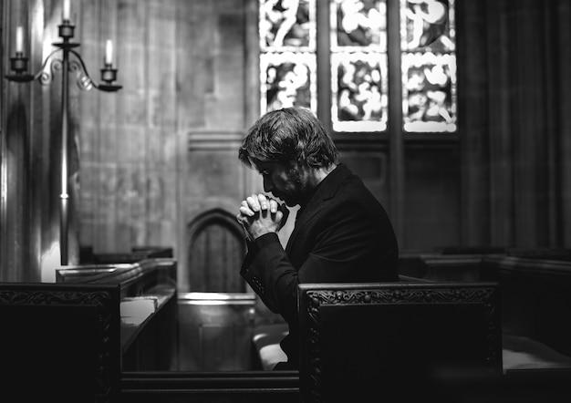 Hombre cristiano solitario rezando en la iglesia.