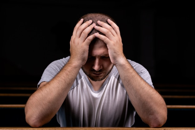 Un hombre cristiano triste con camisa blanca está sentado y rezando con humilde corazón en la iglesia