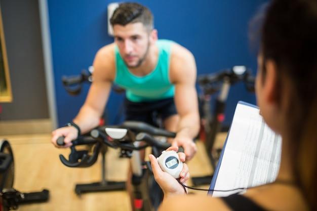 Hombre de cronometraje de entrenador en bicicleta estática