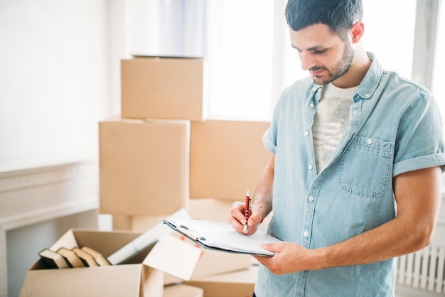 Hombre con cuaderno entre cajas, inauguración de la casa
