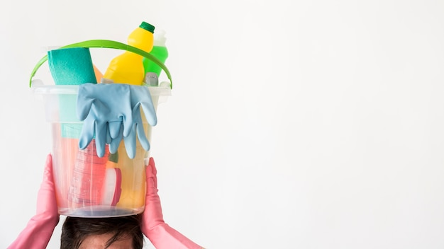 Hombre con cubo de productos de limpieza
