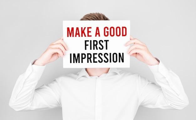 El hombre se cubre el rostro con un papel blanco con el texto haga una buena primera impresión