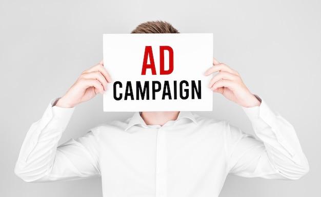 El hombre cubre su rostro con un libro blanco con campaña publicitaria de texto