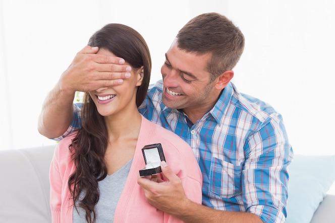 Hombre cubriendo los ojos de la mujer mientras regala el anillo