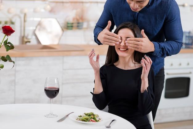 Hombre cubriendo los ojos de su novia con espacio de copia