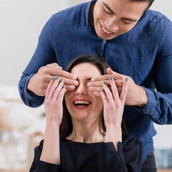 Hombre cubriendo el primer plano de los ojos de su novia