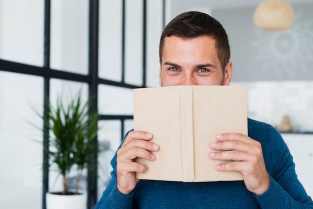 Hombre cubriéndose la cara con un libro en casa
