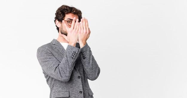 Hombre cubriéndose la cara con las manos, mirando entre los dedos con expresión sorprendida y mirando a un lado