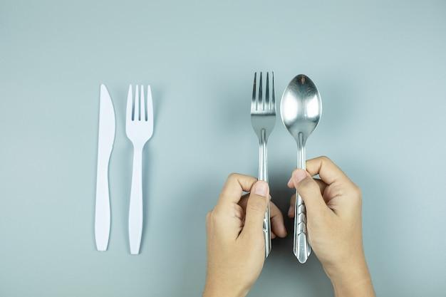 Hombre con cuchara de acero inoxidable y tenedor sobre herramienta de plástico blanco. protección del medio ambiente, cero residuos, reutilizable, decir no plástico, concepto del día mundial del medio ambiente y del día de la tierra