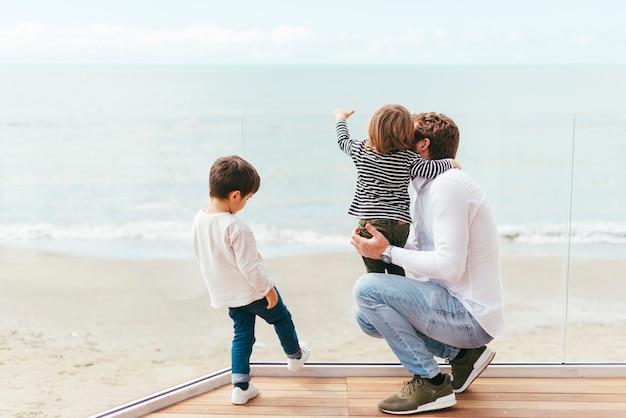 Hombre en cuclillas con niño en la orilla del mar
