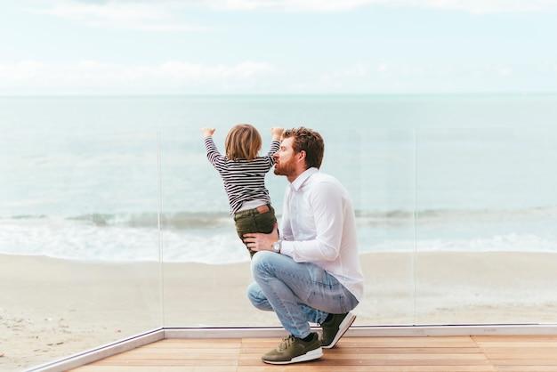 Hombre en cuclillas que sostiene al niño curioso en la costa