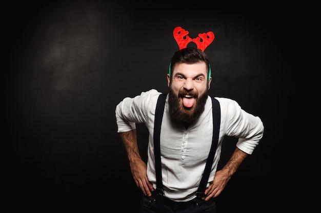 Hombre en cuernos de ciervo falsos mostrando lengua sobre negro.