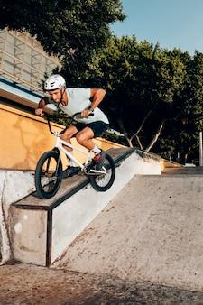 Hombre cuidadoso montando bicicleta vista de ángulo bajo