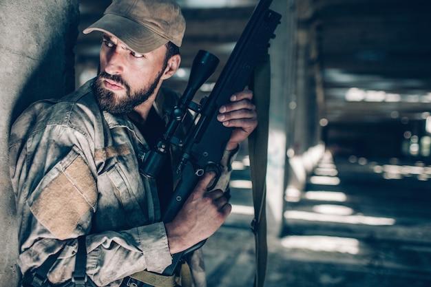 El hombre cuidadoso y valiente está sentado muy cerca de la columna y sostiene el rifle con ambas manos. también está manteniendo el dedo en el gatillo. el hombre lleva uniforme. el esta esperando.