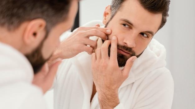 Hombre cuidando bien su rostro en casa
