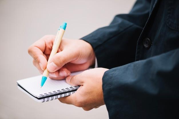 Hombre de cultivos haciendo notas en el cuaderno