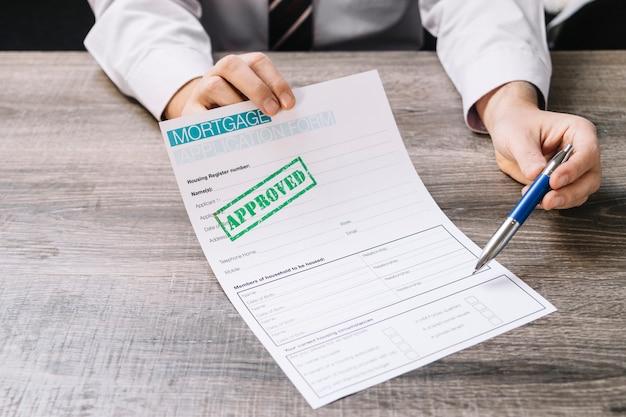 Hombre de cultivos pidiendo firmar papel de hipoteca