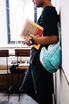 Hombre de cultivos con pie de libro en el aula