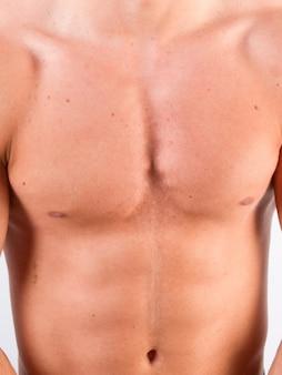 Hombre culturista con abdominales perfectos, hombros, bíceps, tríceps y pecho, entrenador personal de fitness