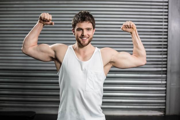 Hombre culturista flexionando sus músculos en el gimnasio