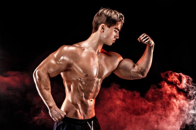 Hombre culturista fuerte con abdominales perfectos, hombros, bíceps, tríceps, pecho posando en humo manos arriba.