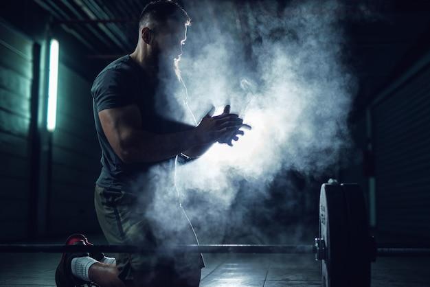 Hombre culturista fuerte de fitness activo trabajador agachado y aplaudiendo con polvo de tiza antes del entrenamiento de fuerza con una mancuerna de peso pesado.