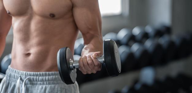 Hombre culturista levantando pesas en el gimnasio de deporte, concepto de culturismo y musculación de cerca.