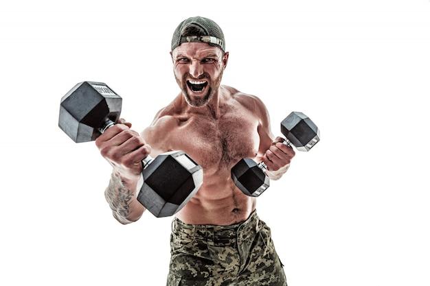 Hombre culturista musculoso atleta en pantalones de camuflaje con un torso desnudo golpeando con pesas como boxer en un blanco