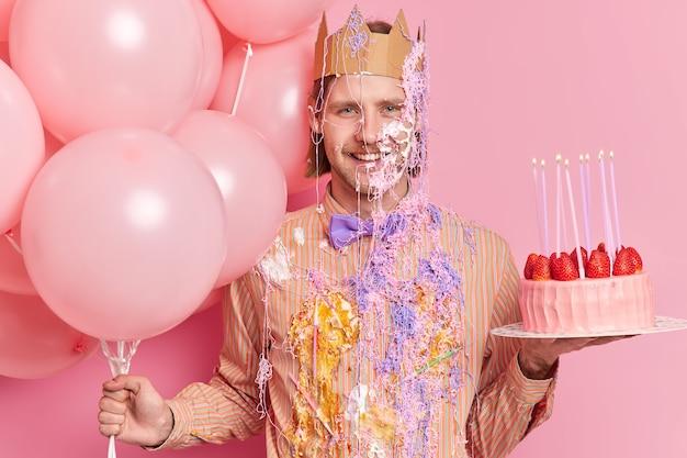 El hombre de cumpleaños alegre con expresión alegre usa corona de papel, ropa festiva sucia, sostiene poses de pastel y globos en la fiesta contra la pared rosa, celebra aniversario o obtiene una nueva posición