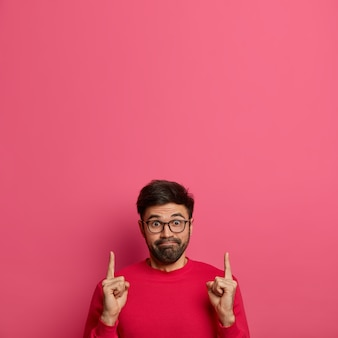 Hombre curioso impresionado presiona los labios, anuncia el producto, señala arriba con ambos dedos índices