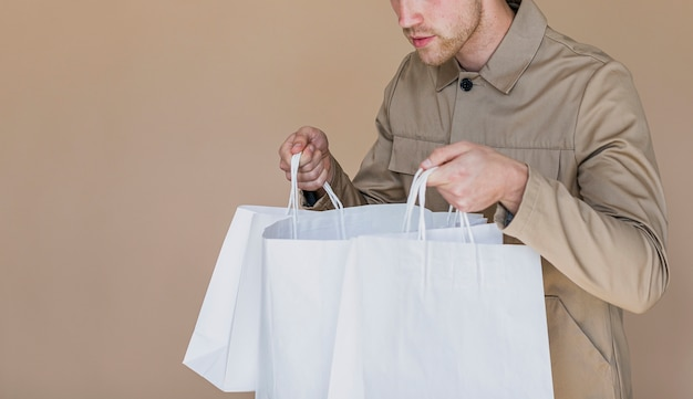 Hombre curioso mirando en bolsas de compras