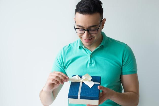 Hombre curioso vistiendo polo camiseta y desenvolviendo caja de regalo
