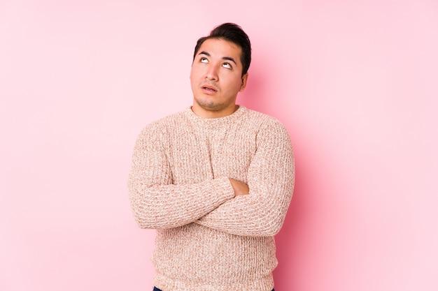 Hombre con curvas joven que presenta en una pared rosada aislada cansada de una tarea repetitiva.