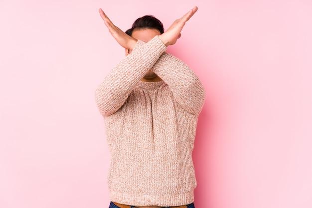Hombre con curvas joven que presenta en una pared rosada aislada manteniendo dos brazos cruzados, concepto de la negación.