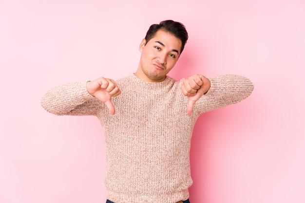 Hombre con curvas joven que presenta en una pared rosada aislada mostrando el pulgar hacia abajo y expresando aversión.