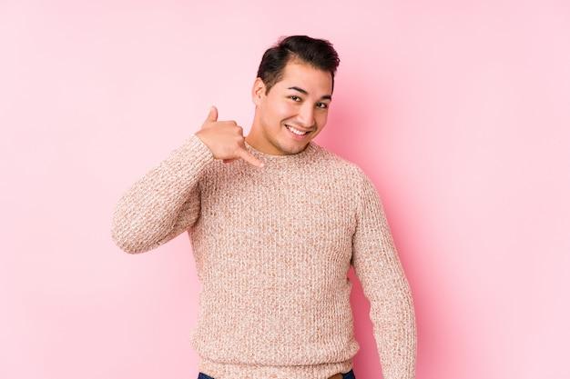 Hombre con curvas joven que presenta en una pared rosada aislada que muestra un gesto de la llamada de teléfono móvil con los dedos.