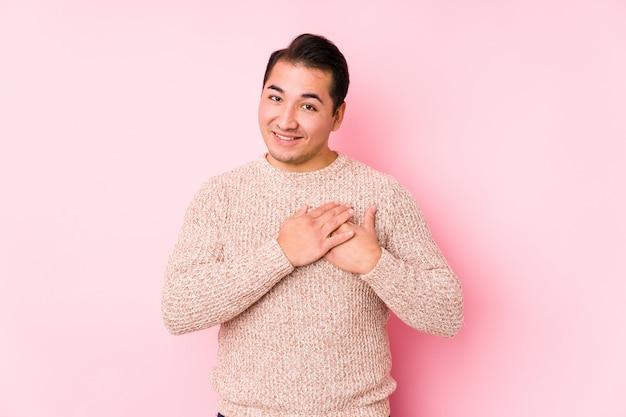 El hombre con curvas joven que presenta en una pared rosada aislada tiene una expresión amistosa, presionando la palma contra el pecho. concepto de amor