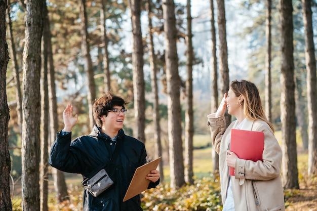 El hombre da choca esos cinco a la mujer en el bosque