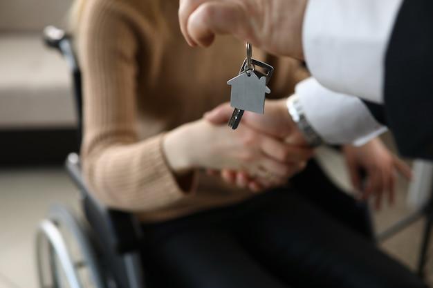 El hombre le da la mano a la persona discapacitada, llave de la casa