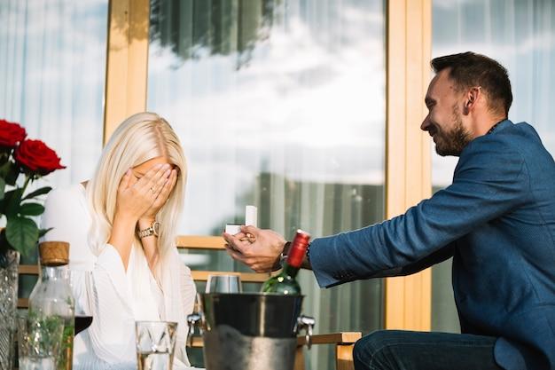 Hombre dando anillo de compromiso a su novia tímida