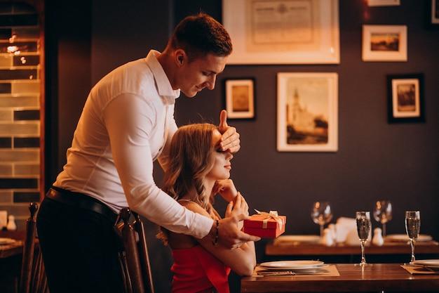 Hombre dando una caja de regalo en el día de san valentín en un restaurante.