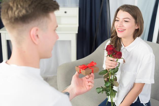 Hombre dando caja de regalo pequeña a mujer feliz