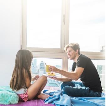 Hombre dando desayuno a su hija en la mañana